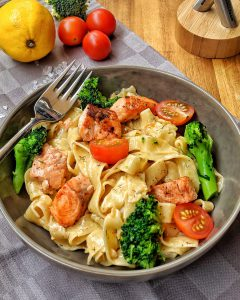 Ein Teller mit Nudeln und Lachs in Sahnesoße. Dabei sind Brokkoli und Tomaten.