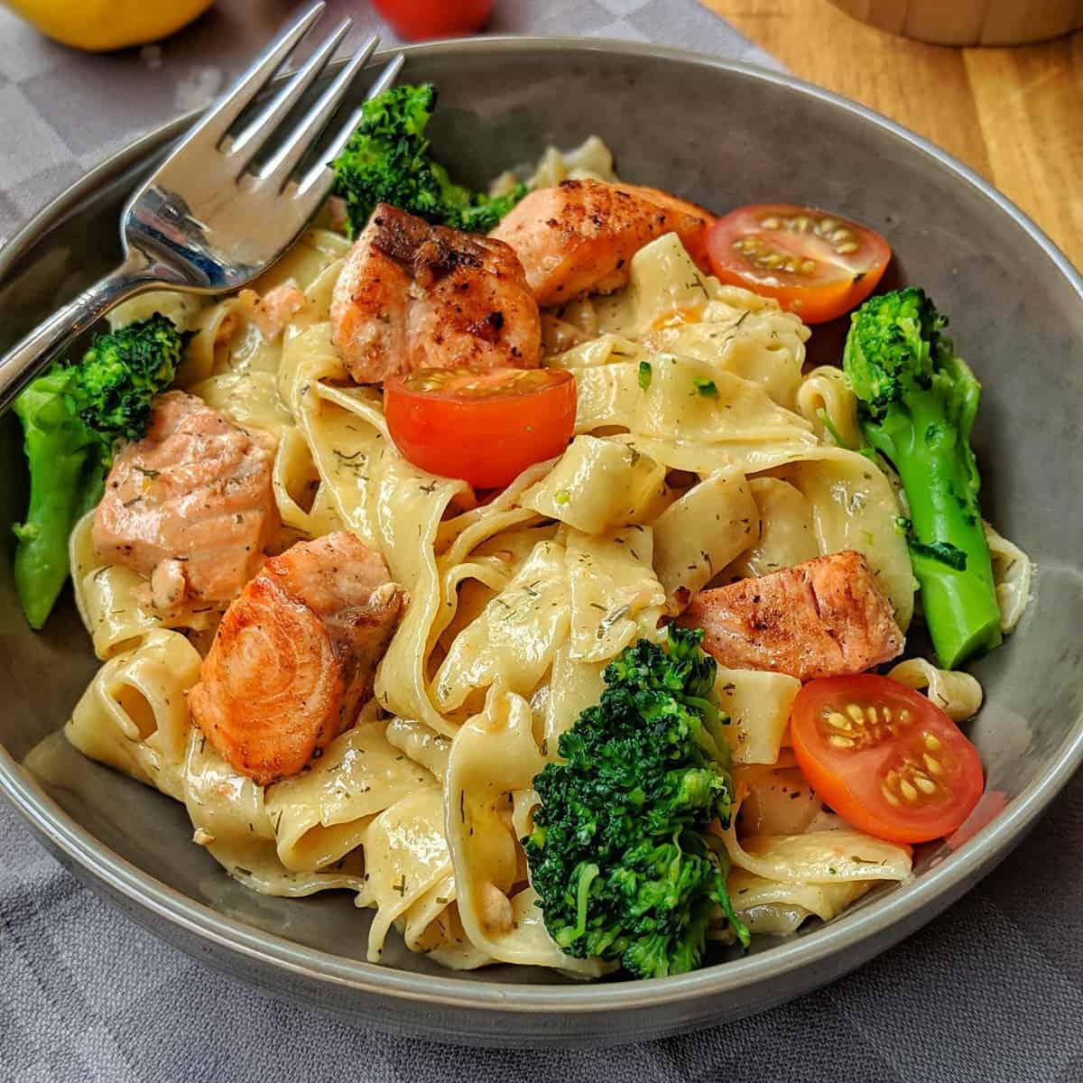 Ein Teller mit Nudeln und Lachs in Sahnesoße mit Brokkoli und Tomaten.