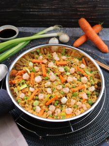 Gebratener Reis mit Shrimps in einer Pfanne, dahinter Deko.