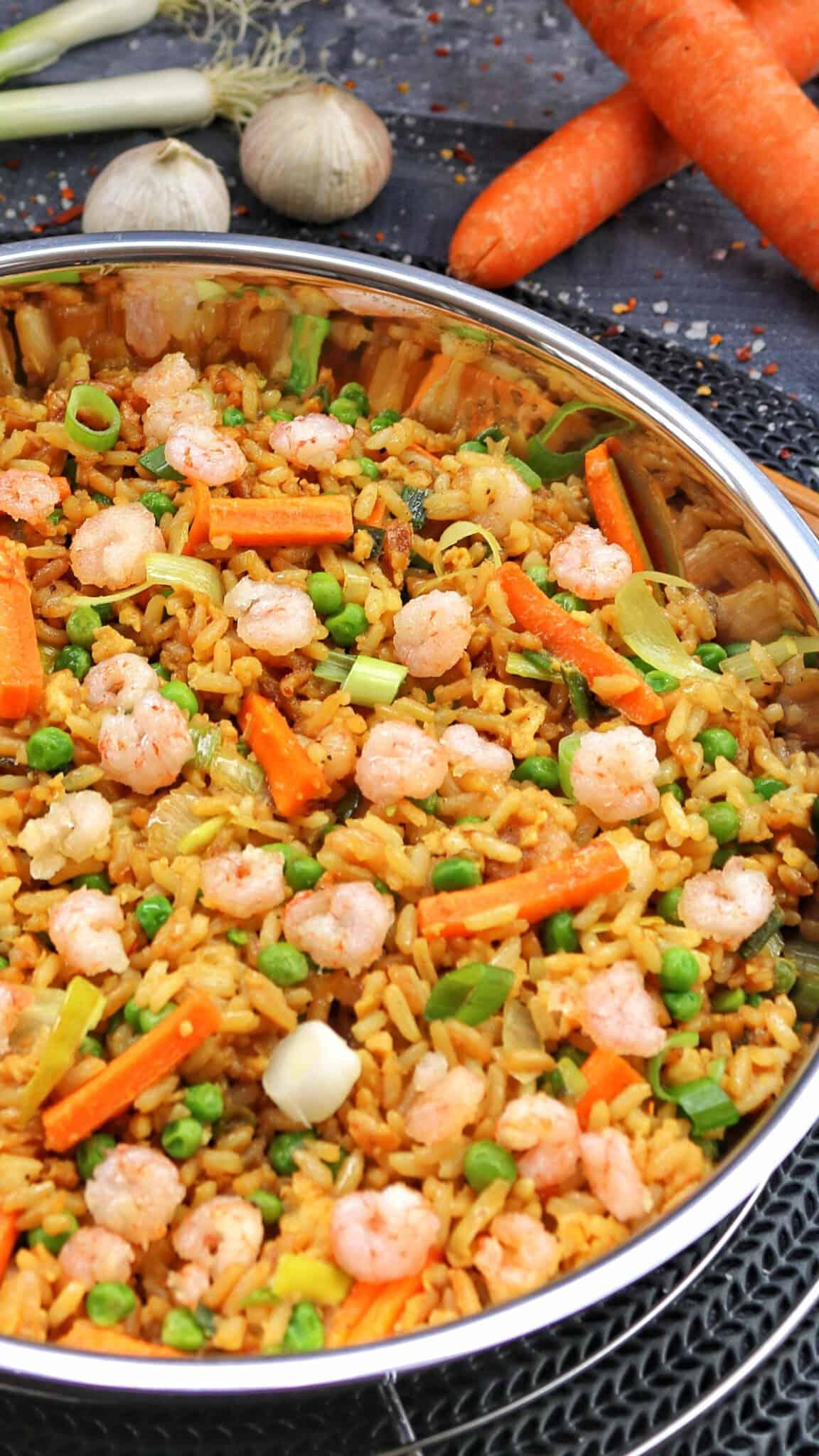 Eine Pfanne mit gebratenem Reis und Shrimps. Dahinter Deko.
