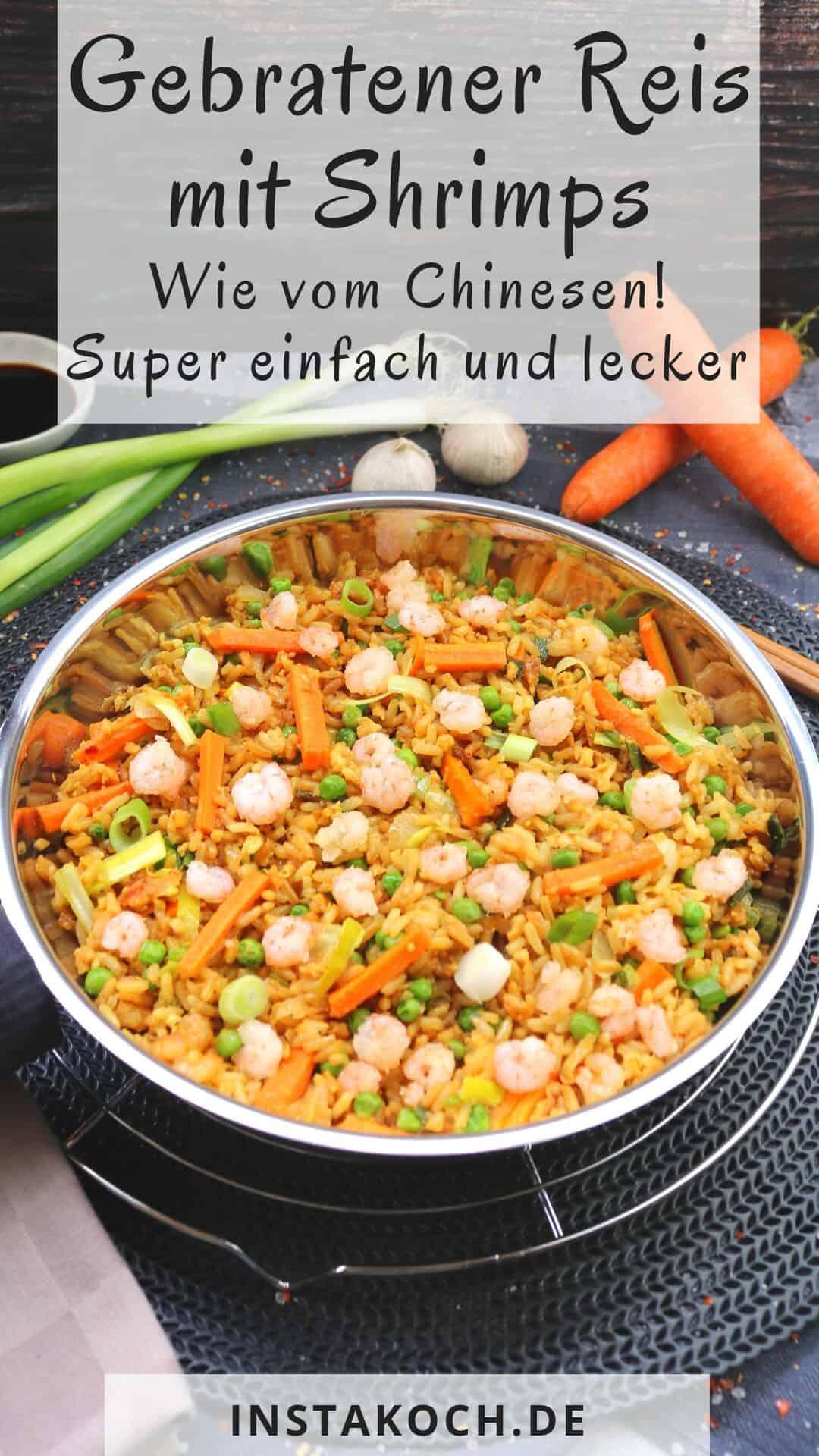 Gebratener Reis mit Shrimps in einer Pfanne. Dahinter Deko.