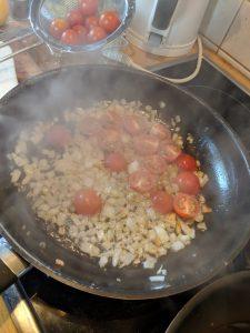 Zweibeln Knoblauch und Tomaten in der Pfanne anbraten