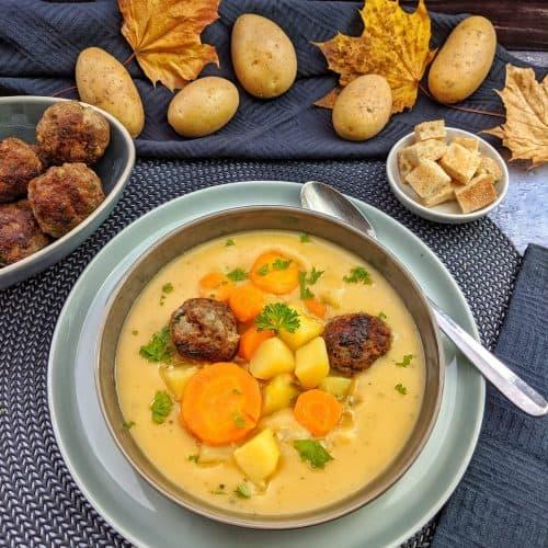 Ein Teller Kartoffelsuppe mit Gemüse und Hackbällchen. Im Hintergrund Deko.