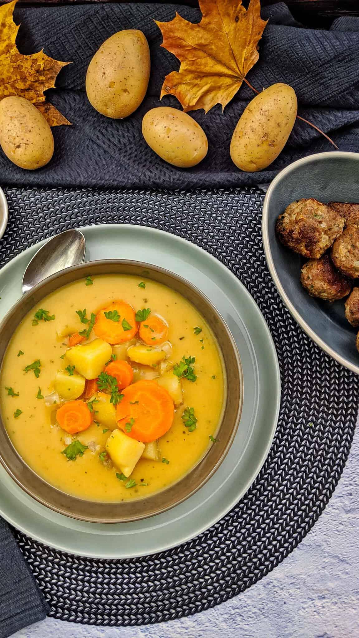 Ein Teller Kartoffelsuppe mit Gemüse. Daneben eine Schale mit Hackbällchen.