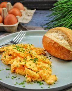 Rührei mit einem Brötchen auf einem Teller. Im Hintergrund Eier und Schnittlauch als Deko.