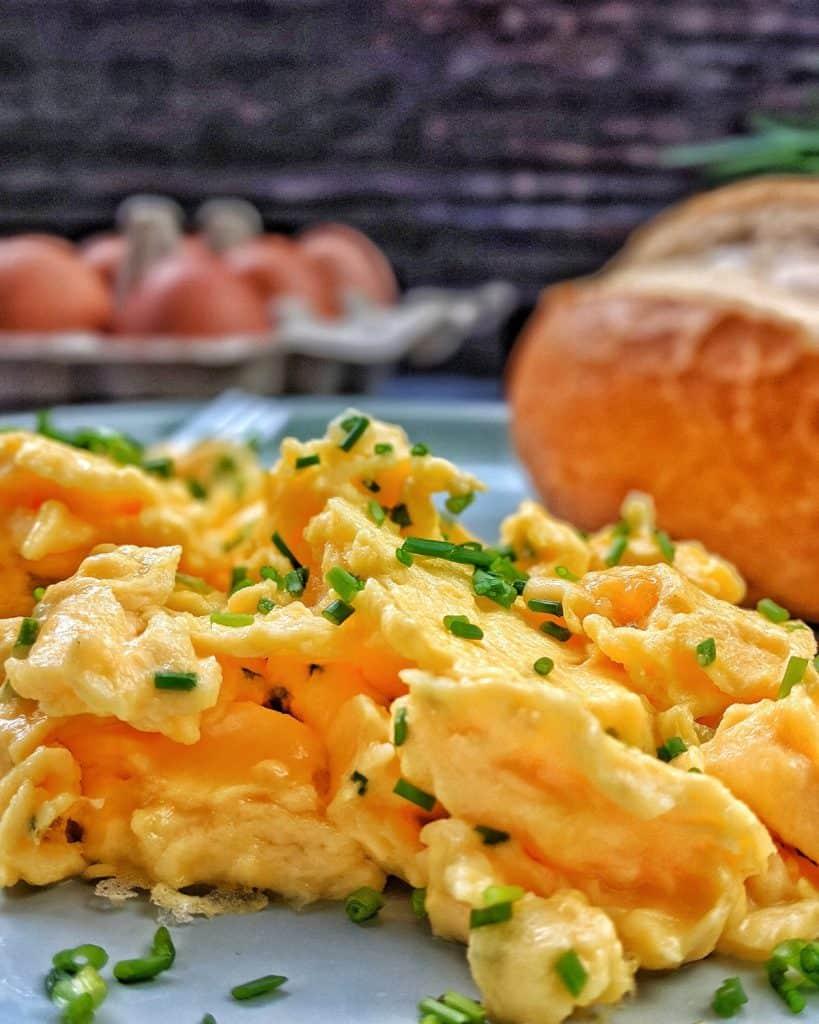 Rührei mit Schnittlauch in Nahaufnahme. Im Hintergrund ein Brötchen und Eier.