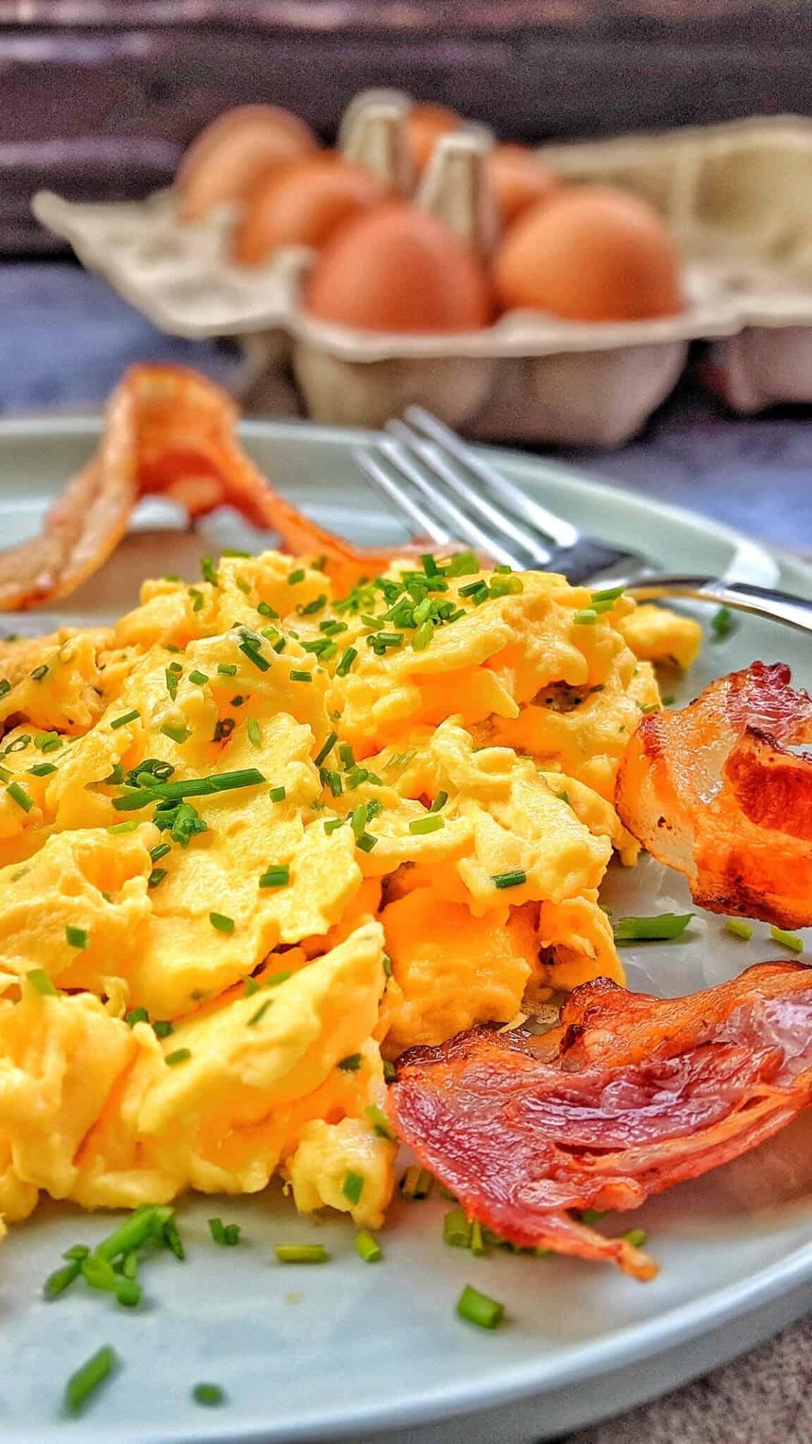 Ein Teller mit Rührei und Bacon. Im Hintergrund ein Packung Eier als Deko.