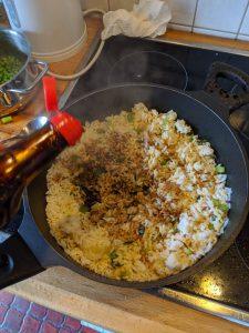Sojasoße wird zum Reis in die Pfanne gegeben.