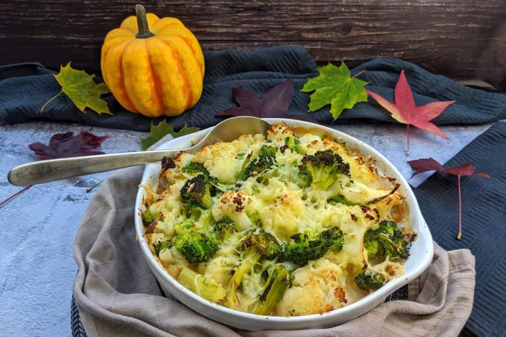 Vegetarischer Blumenkohl-Brokkoli Auflauf mit Kartoffeln und Lauch. Dahinter Deko.