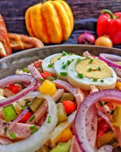 Eine Nahaufnahme vom Wurstsalat. Im Hintergrund ist Kürbis, Paprika und Zwiebeln als Deko.