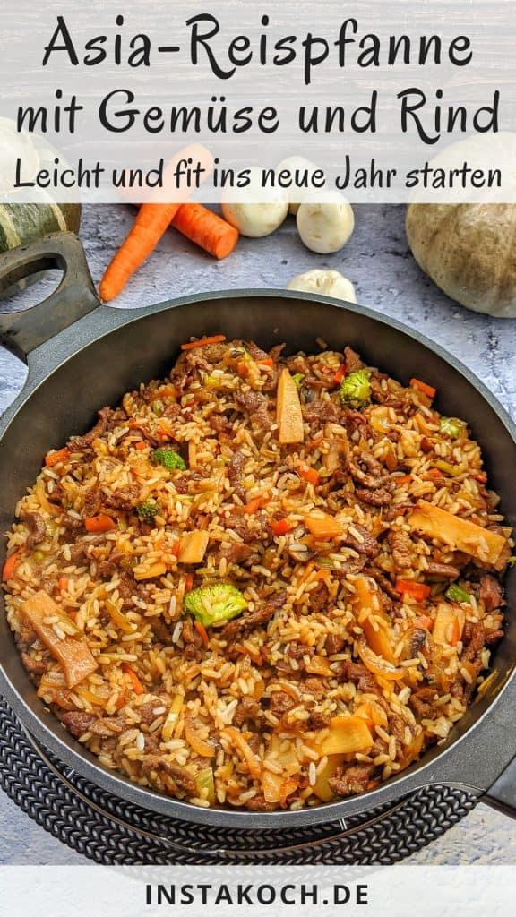 Eine asiatische Reispfanne mit Gemüse und Rindfleischstreifen. Im Hintergrund Deko.