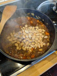 Eine Pfanne in der Bohnen zum Fleisch und Gemüse hinzufügt worden sind.