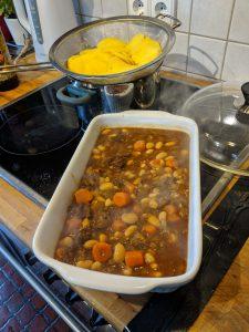 Eine Auflaufform mit Fleisch und Gemüse. Im Hintergrund Kartoffelscheiben in einem Sieb.