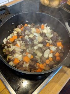 Eine Pfanne mit Fleisch, Zwiebeln, Karotten und Knoblauch.