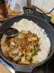 Gemüse kommt zum Reis in eine Pfanne