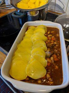 Kartoffelscheiben werden in einer weissen Auflaufform über das Fleisch und Gemüse geschichtet.