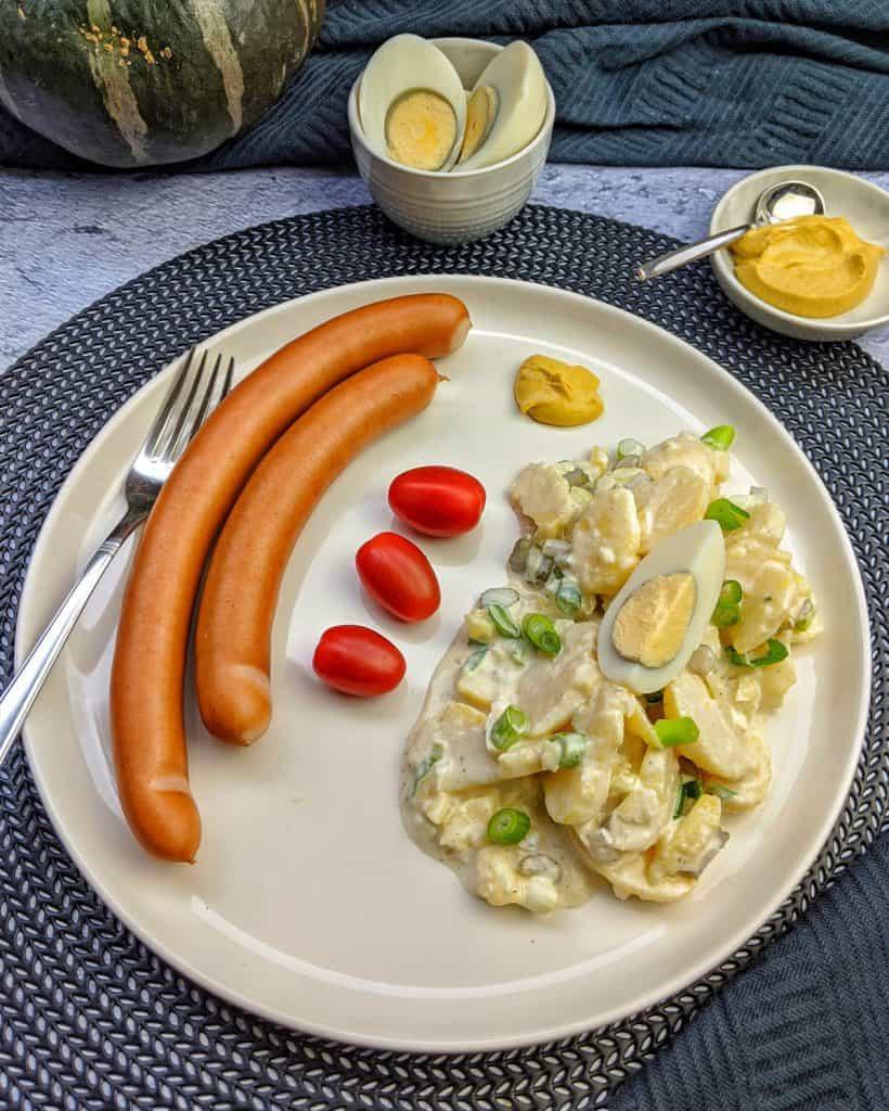 Kartoffelsalat mit Würstchen auf einem Teller. Dahinter Deko.