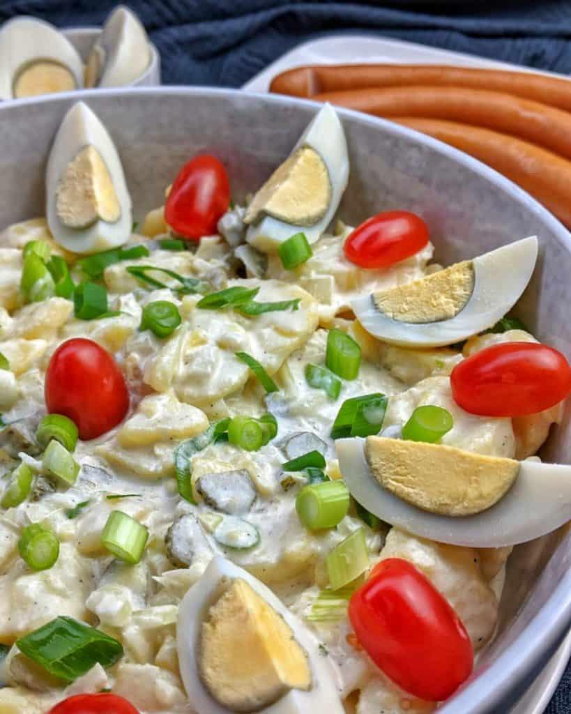 Eine Nahaufnahme von einer Schüssel Kartoffelsalat. Dahinter Würstchen.