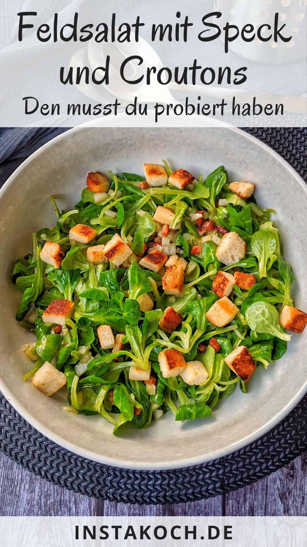 Eine Schüssel mit Feldsalat mit Speck und Croutons