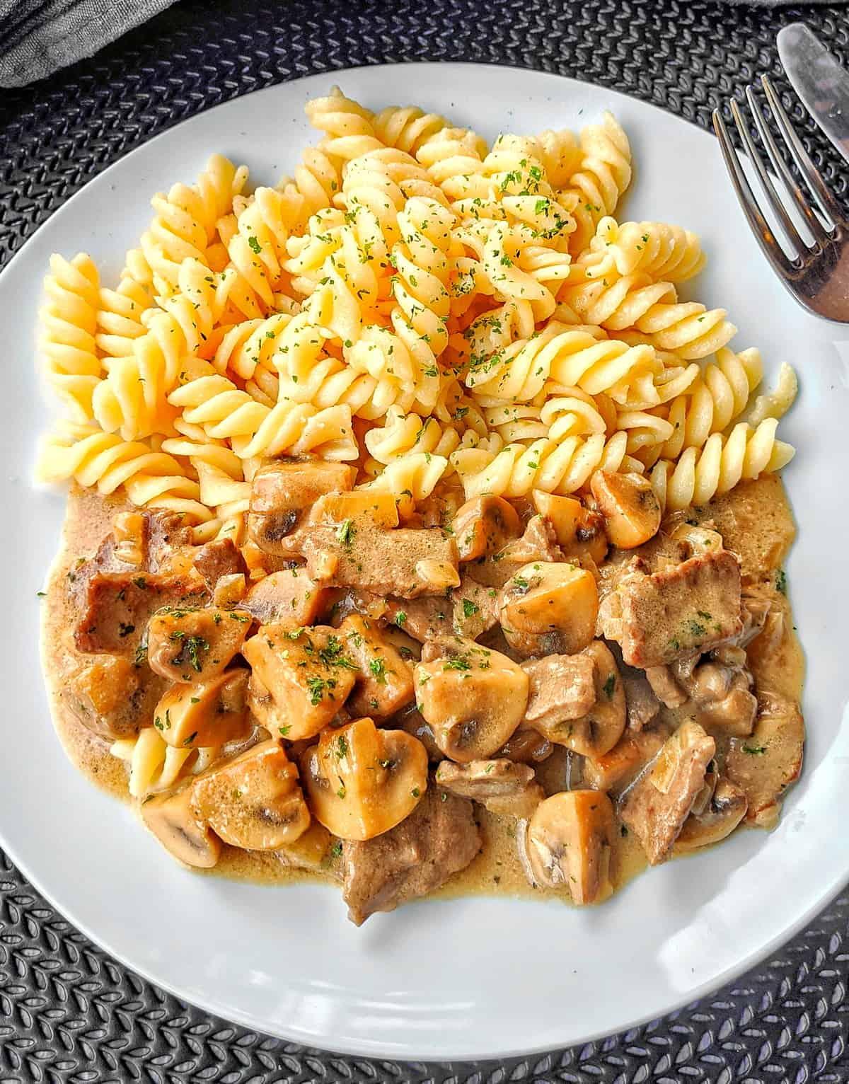 Ein weisser Teller mit Rindergeschnetzeltem in Pilzrahmsoße und Nudeln.