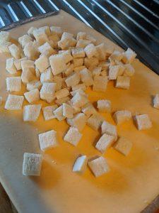 Vorbereitete Weissbrot-Würfel auf einem Schneidebrett