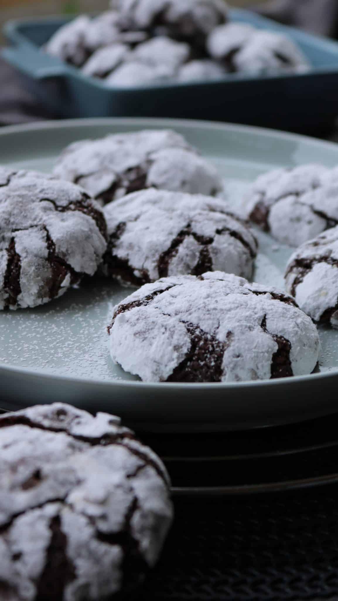 Chocolate crinkle cookies auf einem Teller. Dahinter Deko.