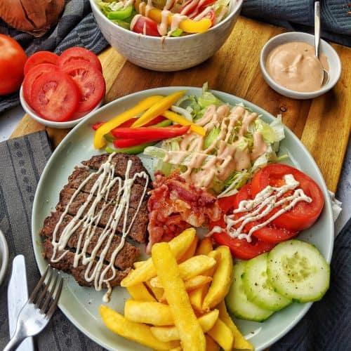 Ein Teller mit einer Burger Bowl. Dahinter eine Schale Salat und weitere Schälchen mit Saucen.