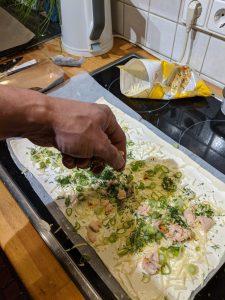 Fisch wird auf dem Blaetterteig verteilt