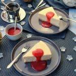 Zwei Teller mit New York Cheesecake mit Fruchtsoße. Daneben Deko.