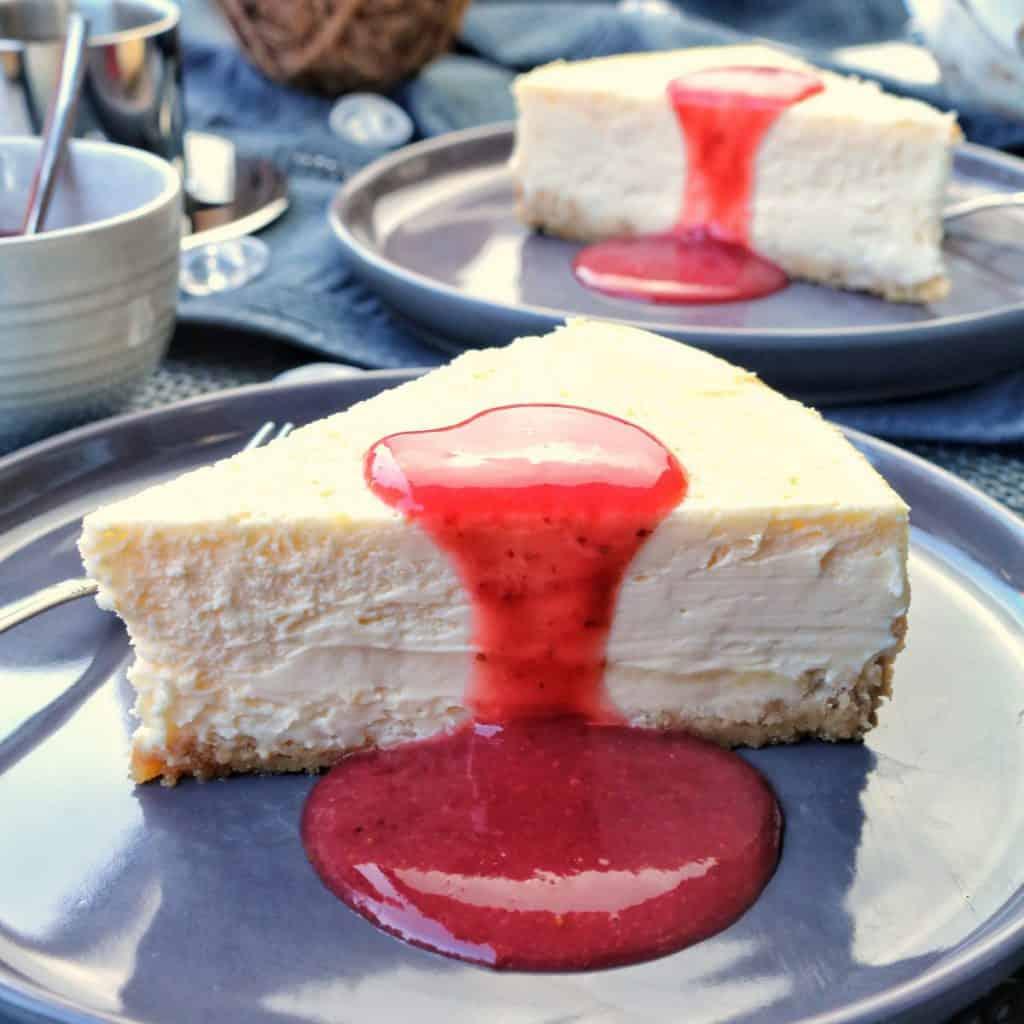 2 Teller mit Cheesecake mit Fruchtsosse. Aussen herum Deko.