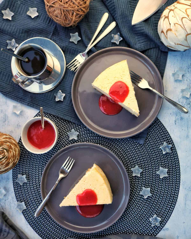 2 Teller mit Cheesecake und Fruchtsosse. Aussen herum Deko.