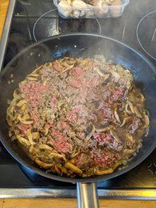 Das Hackfleisch wird zusammen mit Champignons und Zwiebeln in einer Pfanne angebraten.