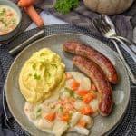 Ein dunkler Teller mit Kohlrabi Karotten Gemüse in heller Soße mit Kartoffelpüree und Bratwurst. Aussen herum Deko.