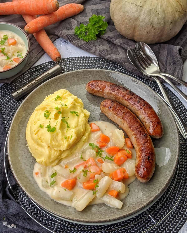 Kohlrabi-Karotten-Gemüse in heller Soße mit Kartoffelpüree und Bratwurst