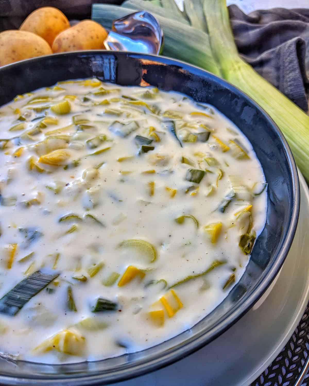 Einen Teller Lauch Gemüse in Heller Sosse. Daneben Lauch und Kartoffeln und Deko.