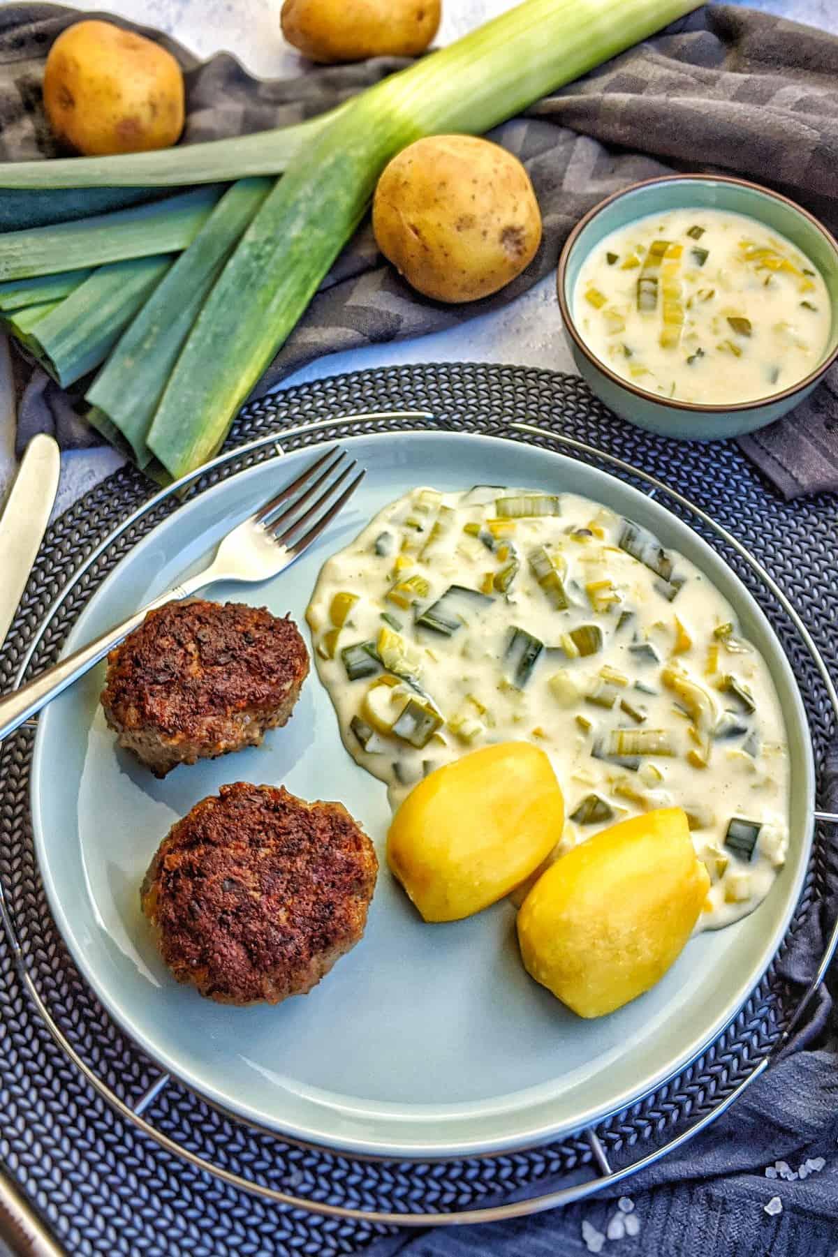 Ein Teller Lauch Gemüse in heller Soße mit Frikadellen.