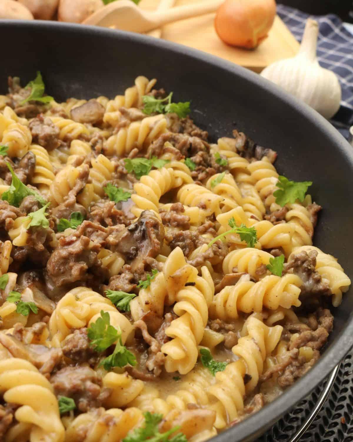Eine Pfanne mit One Pot Pasta mit Hackfleisch und Champignons. Aussen herum Deko.