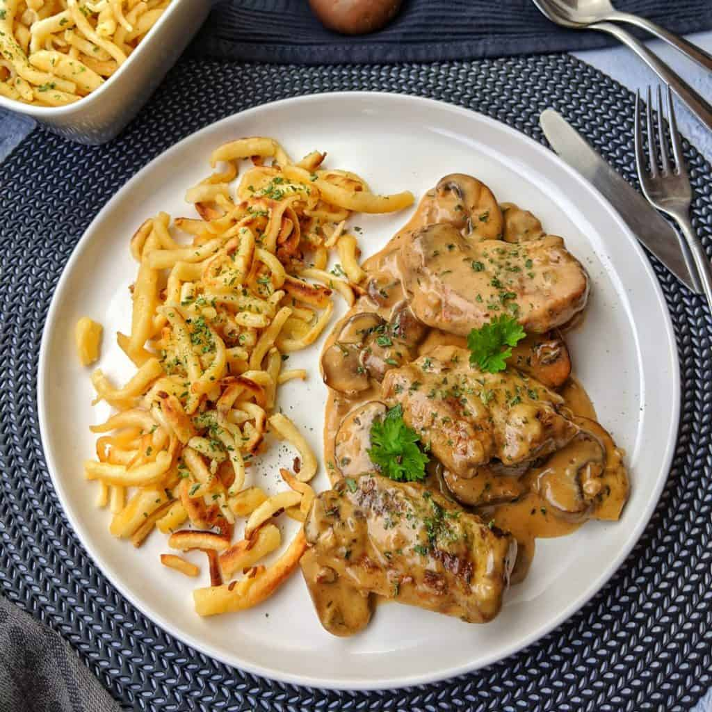 A white plate of pork medallions with a mushroom cream sauce with Spätzle. Behind it's a dish with noodles and decoration.