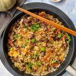 Chop Suey mit Rind und Reis in einer Pfanne. Dahinter Deko und eine Schale mit Sojasoße.