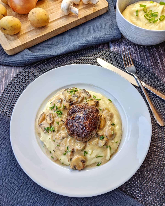 Ein weisser Teller mit Kartoffelbrei, Champignonrahmsoße und Buletten. Dahinter Deko.