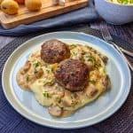 Ein hellblauer Teller mit Kartoffelbrei, Champignonrahmsoße und Buletten. Dahinter Deko.