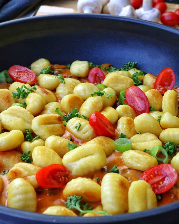 Eine Pfanne mit Gnocchi und Tomaten in Pilzrahmsoße. Dahinter Gemüse als Deko.