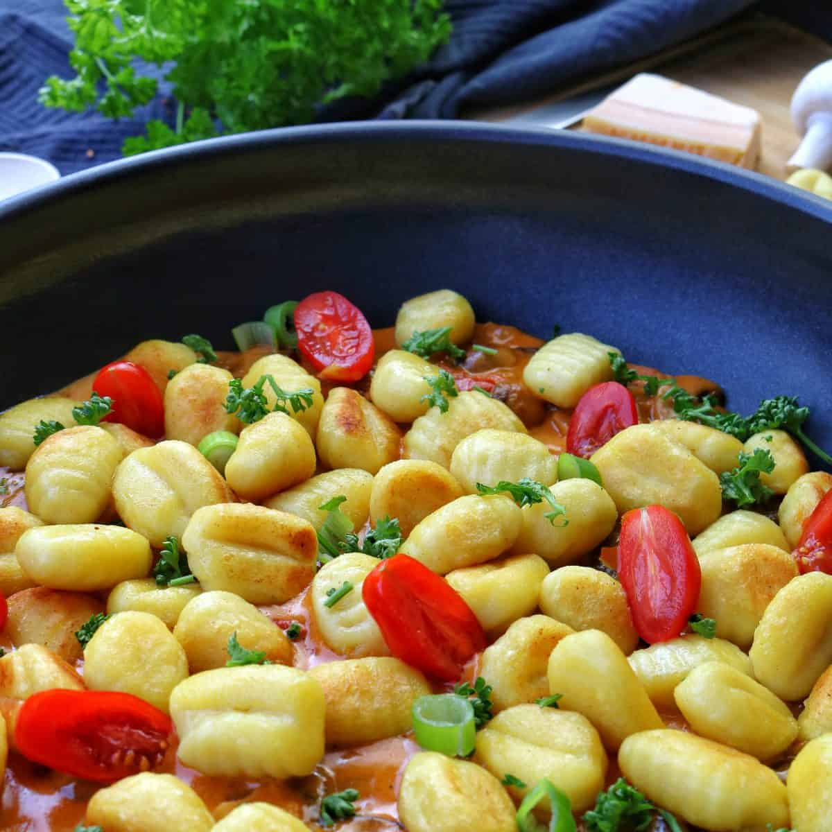 A frying pan with Gnocchi and tomatoes in a mushroom cream sauce. Behind vegetables as decoration.