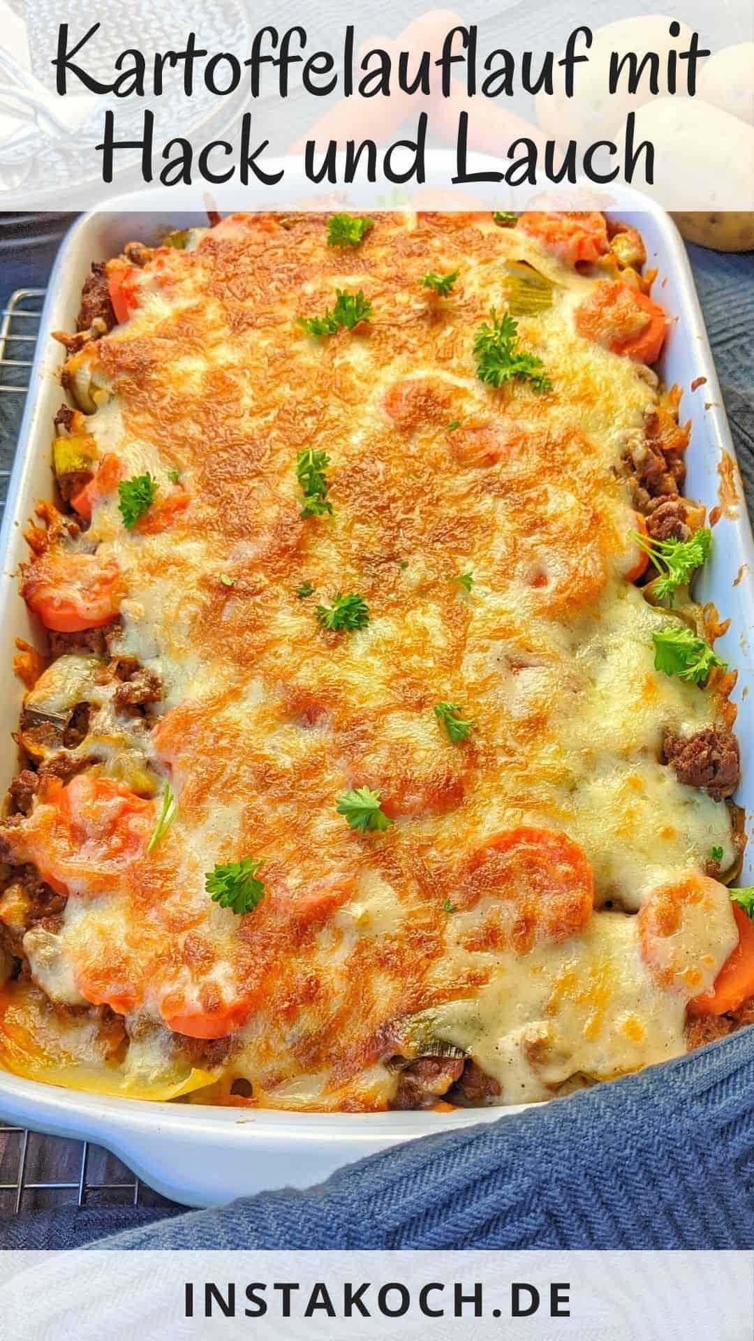 Eine rechteckige weisse Auflaufform mit dem fertigen Gericht. Dahinter Teller, Besteck und Gemüse als Deko.