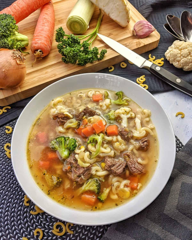 Ein heller tiefer Teller mit Nudelsuppe mit Rindfleisch. Im Hintergrund Deko.