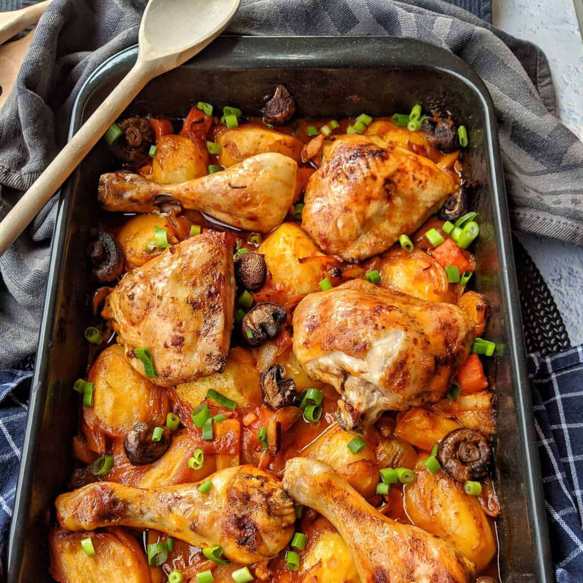 A casserole dish with oven-fried chicken with potatoes and vegetables in tomato sauce