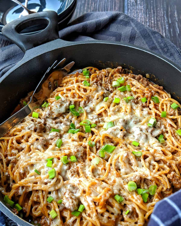 Eine dunkle Pfanne mit dem one pot Spaghetti Gericht und einer Servierkralle für die Nudeln