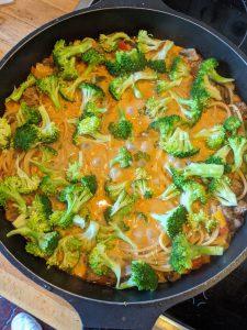 Brokkoli auf das one pot Gericht in einer Pfanne geben