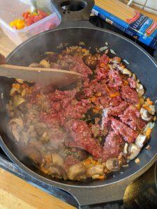 Hackfleisch wird in einer Pfanne zumsammen mit Gemüse angebraten