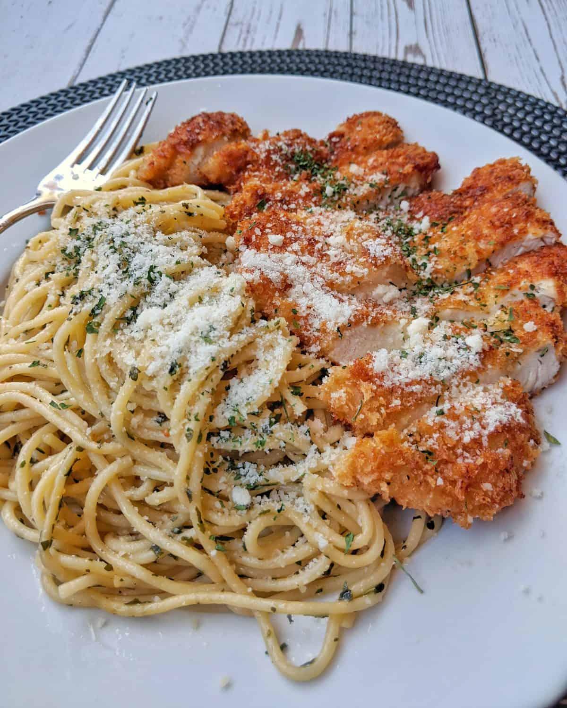 Ein weisser Teller mit Spaghetti Aglio e Olio und einem Hähnchenschnitzel